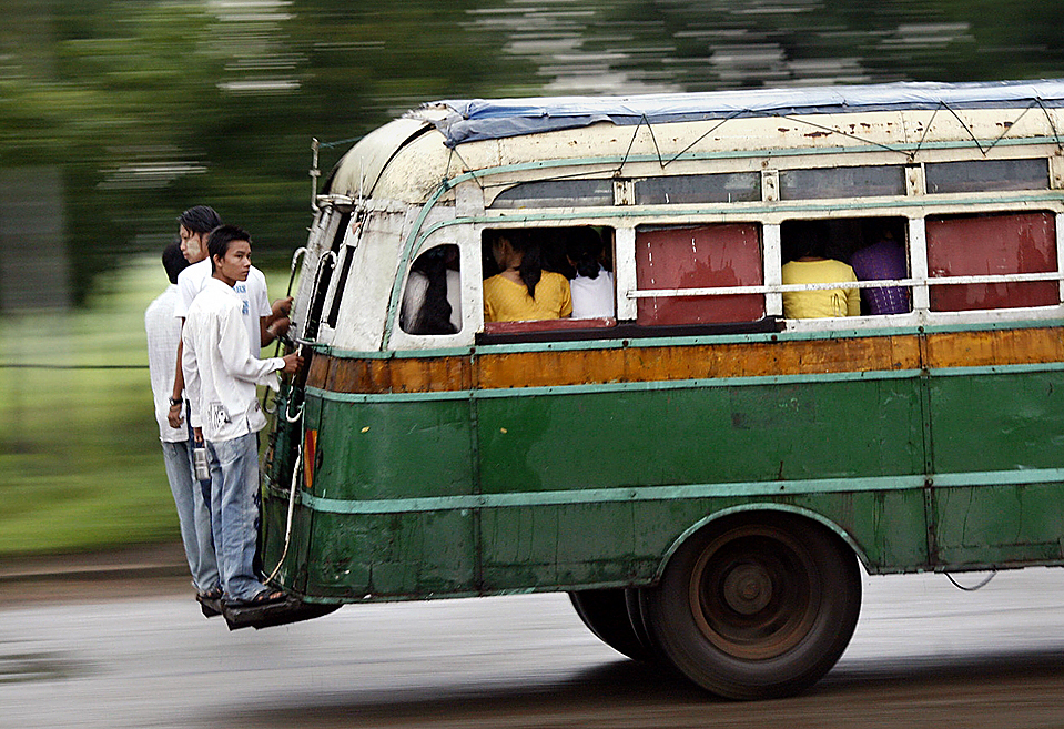 Men stand on the back of a bus while catching a ride on the road from Bago to Yangon
